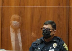 JAMM AQUINO / JAQUINO@STARADVERTISER.COM                                 Honolulu police Sgt. Adam Lipka listens to questions from defense attorney Richard Sing, reflected in the plexiglass barrier, in the district courtroom of judge William M. Domingo during the third day of preliminary hearings for three Honolulu police officers in the killing of Iremamber Sykap, on Tuesday, in Honolulu.