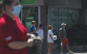 JAMM AQUINO / JUNE 30                                 Pedestrians wait to cross South King Street in June. Hawaii's visitor industry continued to recover in July aided by the domestic market, which was up strong-double digits from pre-pandemic times.