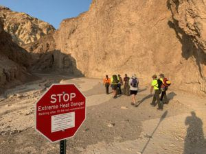"""NATIONAL PARK SERVICE VIA AP / AUG. 18                                 In this Wednesday, Aug. 18, 2021, photo provided by the National Park Service, an inter-agency search and rescue crew walks past a sign reading"""" """"Stop, Extreme Heat Danger,"""" with park rangers responding on foot near Red Cathedral along the Golden Canyon Trail in Death Valley National Park, Calif."""