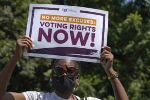 ASSOCIATED PRESS                                 LaQuita Howard of Washington, with the League of Women Voters, attends a rally for voting rights near the White House in Washington.