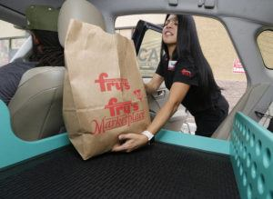 ASSOCIATED PRESS                                 In this 2018 file image, Fry's customer service representative Yuri Alvarado puts groceries into the self-driving Nuro vehicle parked outside a Fry's supermarket, which is owned by Kroger, as part of a pilot program for grocery deliveries in Scottsdale, Ariz. Nuro, the robotics company that develops driverless vehicles for on-road grocery, pizza and prescription deliveries says it will spend $40 million to put a manufacturing facility at the Las Vegas Motor Speedway.