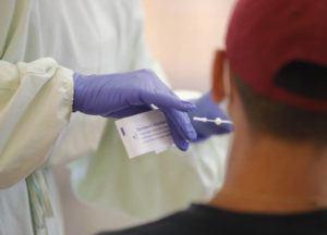 JAMM AQUINO / JAQUINO@STARADVERTISER.COM                                 Project Vision Hawaii nurse Toni Floerke readies a PCR test swab for a patient at Nanakuli High School on Saturday.