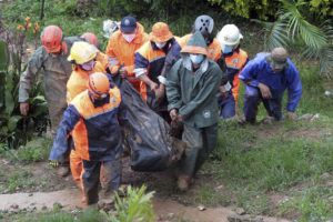 ASSOCIATED PRESS                                 Rescuers carry the body of a victim caught in a landslide caused by Tropical Storm Kompasu in Baguio city, Philippines, on Tuesday.