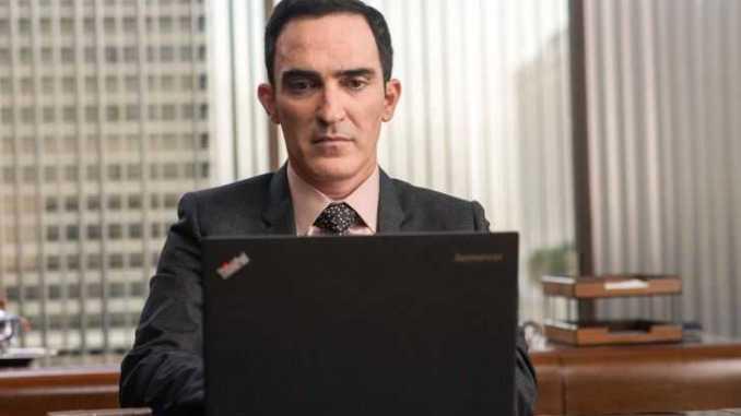 Patrick Fischler working in a laptop.