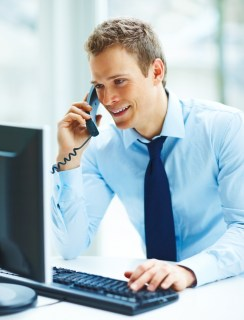Portrait of a young busineass man speaking on the phone while working on a computer