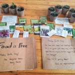 "Sign reading ""food is free"" with seedlings and seeds being given away"