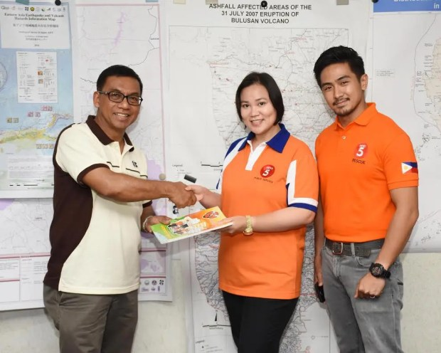 PHIVOLCS Director Renato Solidum, Jr. shakes hands with TV5 Public Service Head Sherryl Yao to seal partnership for Rescue 5 activity book.  Also in photo is Rescue 5 Host Renz Ongkiko.