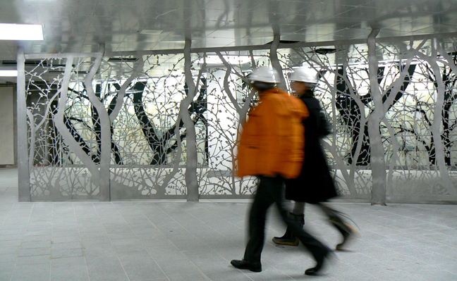 Photo of tree-shaped steel fence in subway station.