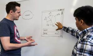 Two men discuss images on whiteboard