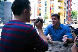 Man holding video camera interviewing another male