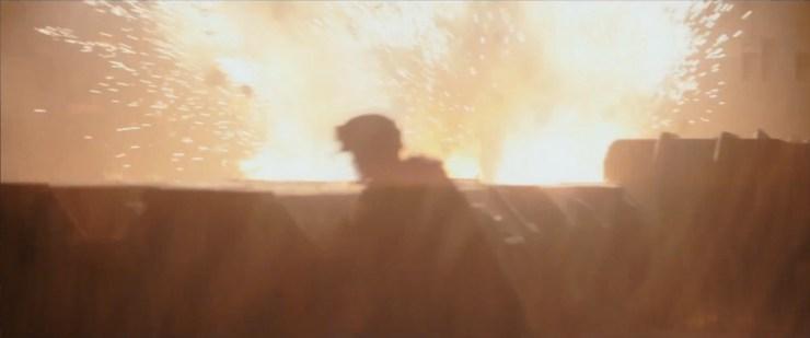Dit shot zagen we ook in de vorige trailer, maar op dat moment viel mij dit persoon nog niet bewust op.<br /> Wanneer de X-Wings door het ravijn vliegen en het vuur openen op de Stormtroopers voor de shuttle van Director Krennic, zien we dit persoon op de voorgrond verscholen zitten achter een aantal kisten.<br /> <br /> De kleding van deze persoon doet ons wel heel erg denken aan de kleding van de Rebellen op Endor.<br /> <br /> Zijn de X-wings een afleiding zodat deze Rebel toegang kan krijgen tot de shuttle?