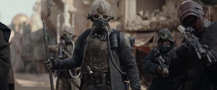 Een shot van een de bende van Saw in de straten van Jedha. Op de achtergrond zien we Edrio Two-Tubes, van wie het kostuum op San Diego Comic Con te zien was.