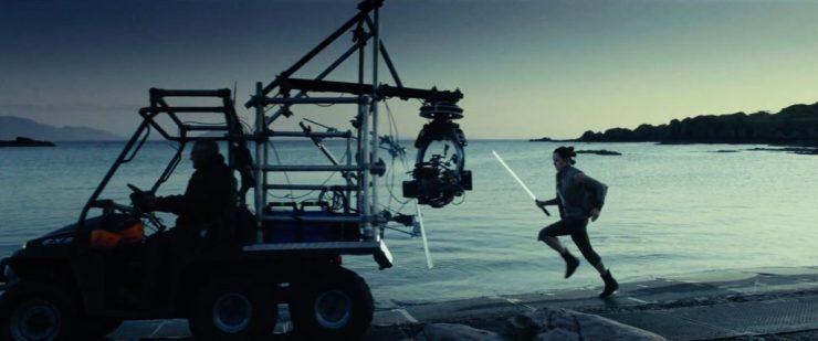Dit is een iets langere versie van een shot dat we eerder al zagen. Rey rent met lightsaber in haar hand langs het water achter de camera aan.