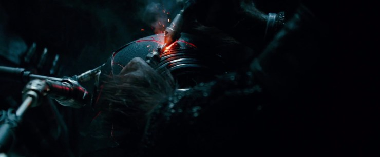 Dan zien we iemand die Kylo Ren's helm aan het repareren is. Ik zeg iemand, want die handen zijn véél te harig om van Kylo te zijn. Aan de andere kant lijken ze weer niet harig genoeg om van Chewbacca te zijn, ook lijkt dit figuur mouwen te hebben, iets waar Chewie nooit een fan van geweest is. Ben sloeg zijn helm in The Last Jedi aan diggelen nadat Supreme Leader Snoke hem belachelijk maakte. Maar nu neemt iemand zorgvuldig de tijd om hem weer in elkaar te zetten, maar alle barsten blijven op een gestileerde manier aanwezig.