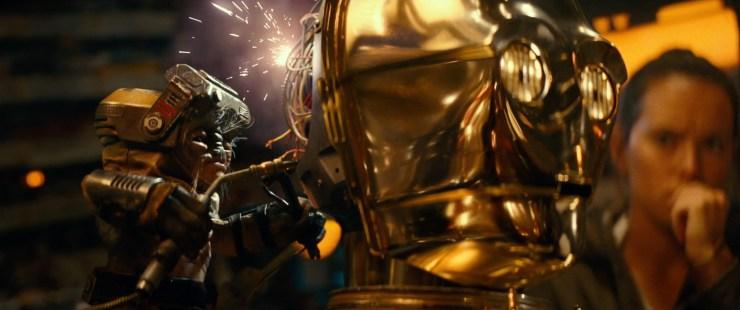 Hier zien we Babu Frik in de hersenpan van C-3PO werken terwijl Rey, Finn, Poe, Zorri Bliss, BB-8 en D-O bezorgd toekijken.