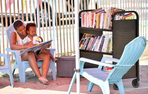 a woman reads a book to a child at a pop-up reading room