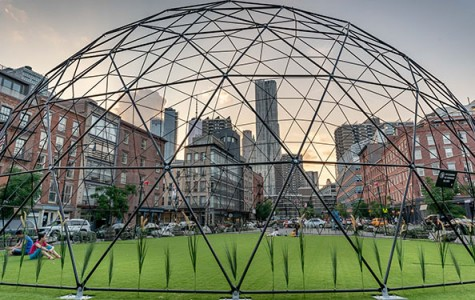 guests hang out on a synthetic turf under a dome in the middle of a plaza surrounded by skyscrapers
