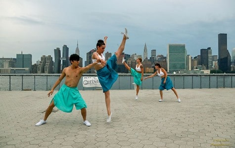 dancers perform at the waterfront of a park