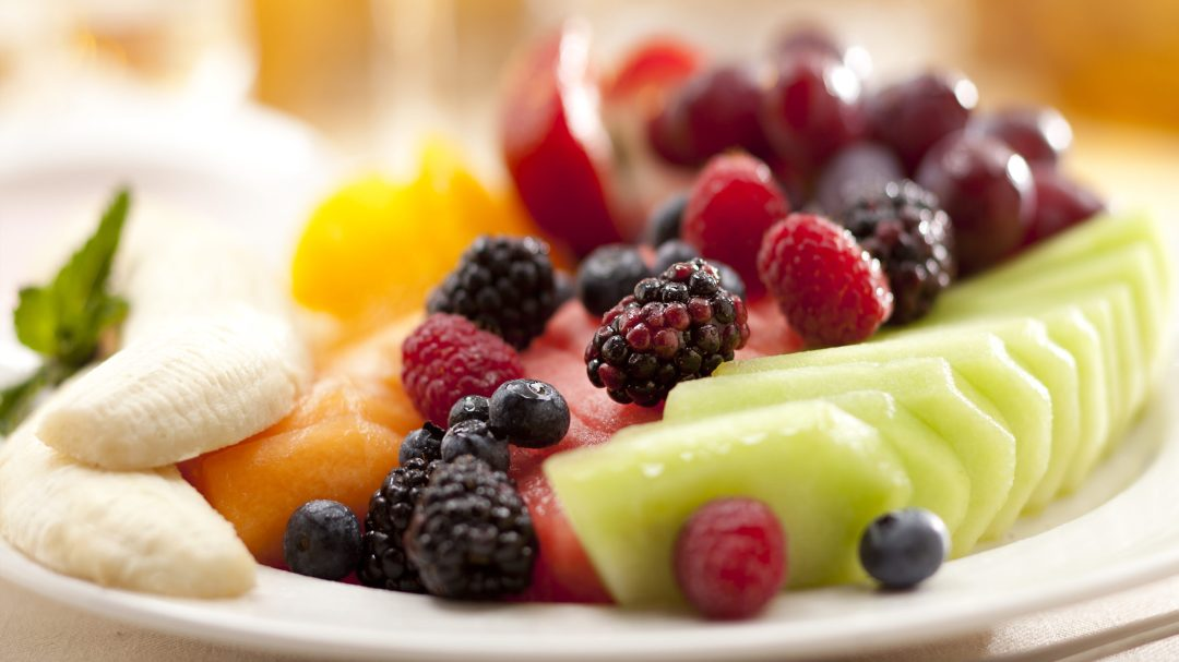 an image of a fruit plate with berries and melons