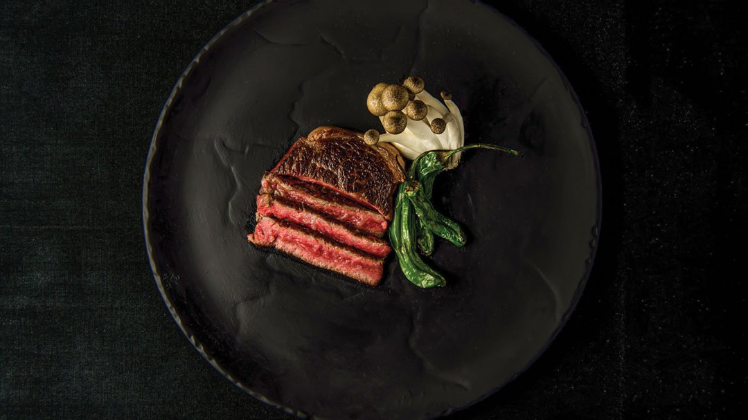an image of steak with mushroom and peppers on a black plate