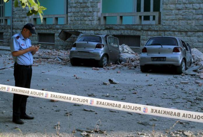 epa07859916 A policeman stands next to the damages of crushed cars next to a building of the University of Geology and Mine, after a 5.8 magnitude earthquake hit in Tirana, Albania, 21 September 2019.