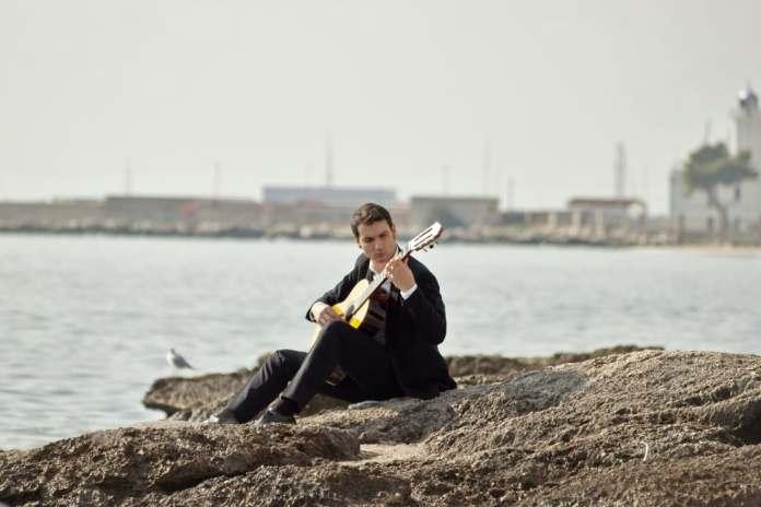 In foto il manfredoniano Ilario Lombardi, musicista e docente di chitarra classica titolare nella scuola pubblica - (Foto scattate sulla scogliera