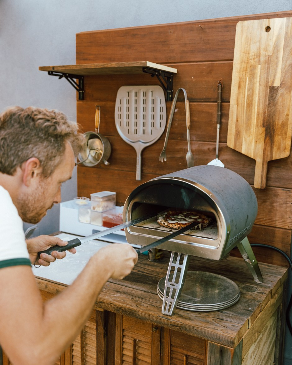 Checking a neapolitan pizza in a rustic outdoor kitchen