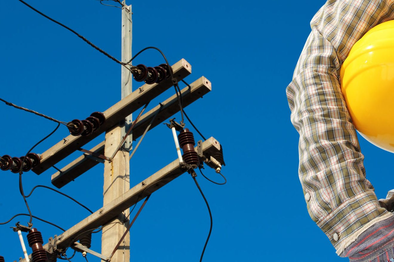 Electrician worker at work against electric post and blue sky background