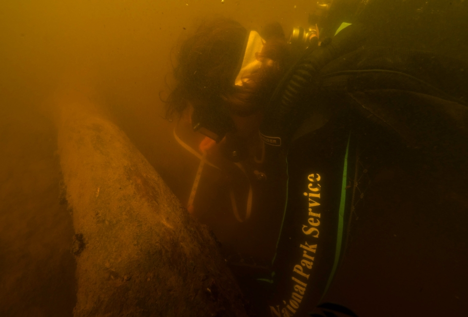 A National Park Service diver examines a historic dam structure in the St. Croix River.
