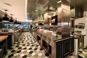 The kitchen is all stainless steel with black overhanging lights