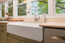 White Kohler apron front farm sink adds to the cottage feel of this kitchen renovation.