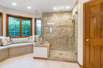 Large luxury master bathroom shower with dual shower heads and frameless glass swinging shower door.