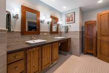 Double vanity with polished granite countertops. Surrounding subway tile and mosaic tile work.