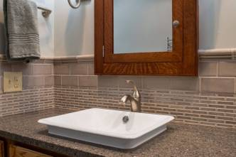 Polished granite countertops and Subway and Mosaic tile surround two vessel sinks.