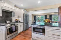 Open concept kitchen features white cabinetry and stainless steel Bosch appliances
