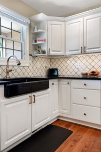 Black Kohler Farmhouse sink along with black quartz countertops help to bring this kitchen together