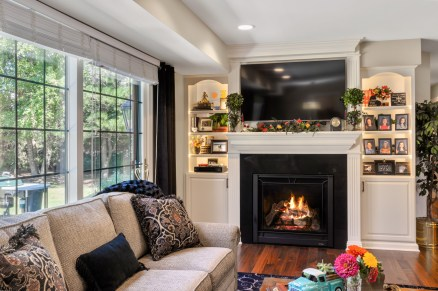 Open concept living room with American walnut hardwood floors, custom mantle, fireplace surround and book case.