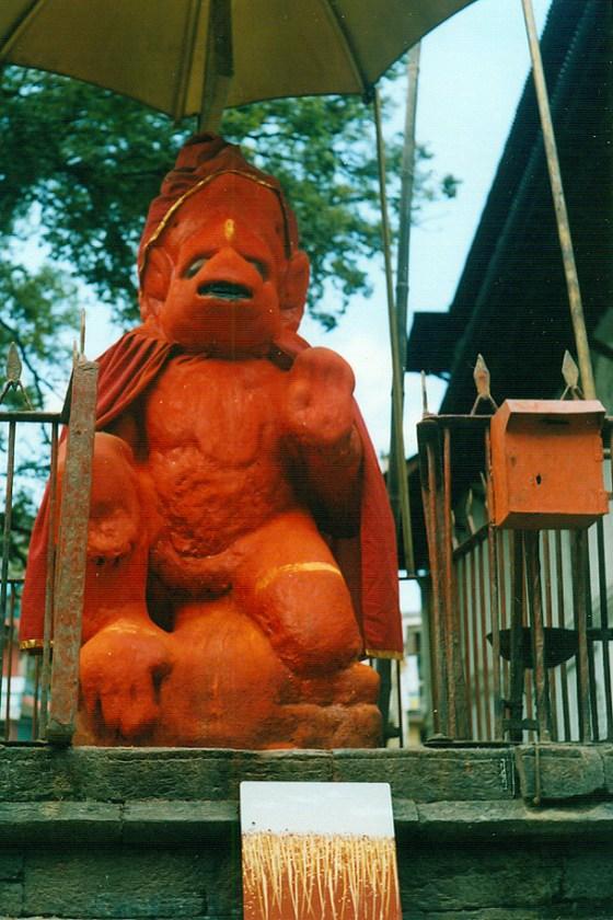 Dono d'arte appoggiato sulle scale di un piccolo tempio dedicato a una divinità scimmia in Nepal