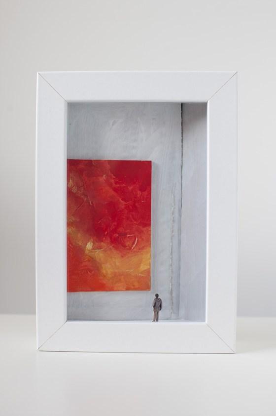 un quadro diorama rappresenta un uomo che osserva un enorme quadro tutto rosso.