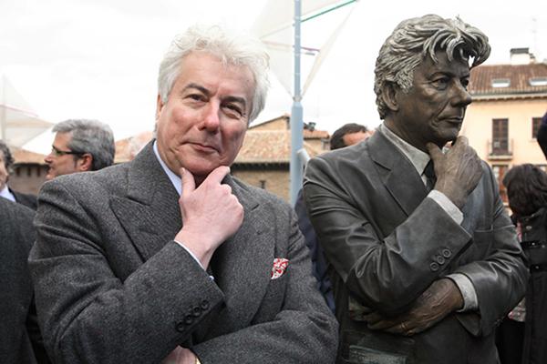 Ken Follett accanto a una statua che lo ritrae