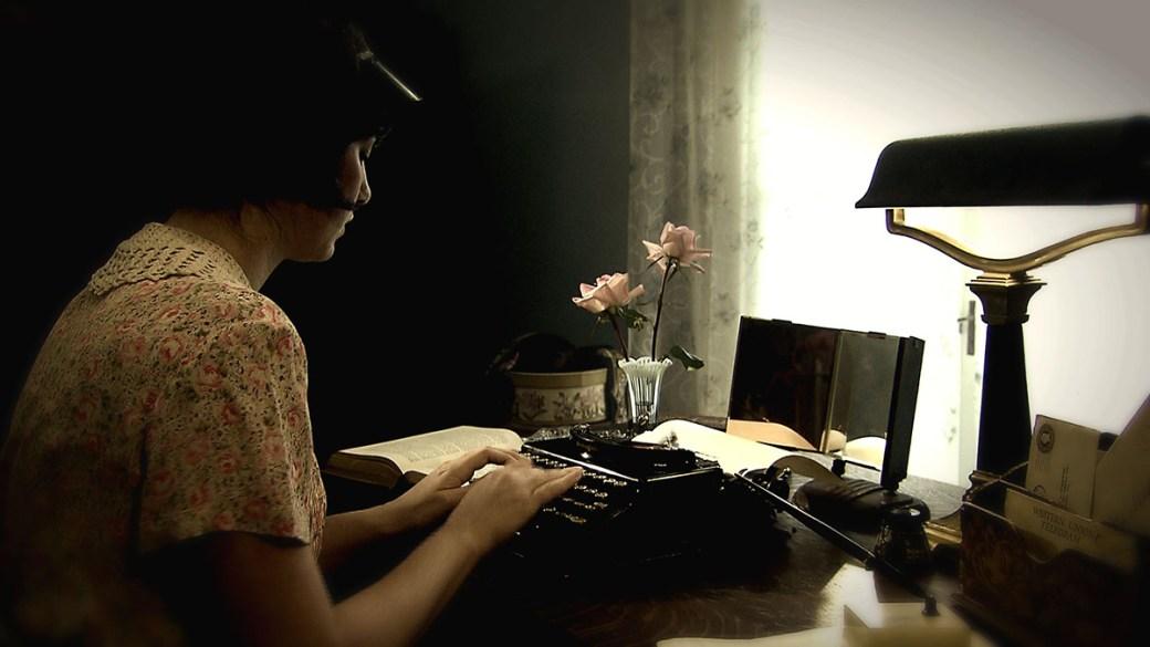 Donna che scrive su una vecchia macchina da scrivere