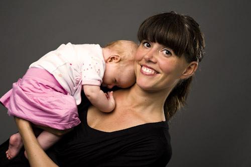 Sovande spädbarn med mamma i fotostudio