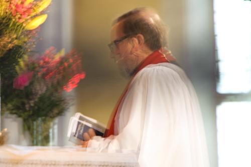 Bröllopsfotografering med suddig präst pga skakningsoskärpa, framme vid altaret
