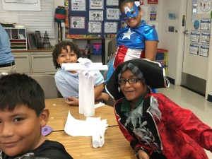 Students dressed as superheroes showing off their strengths at building paper towers