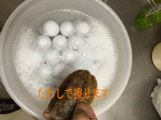 ゴルフボールをたわしで洗う