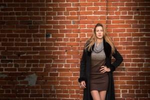 Belle jeune femme avec vêtements d'automne sur un mur-de briques à Montréal