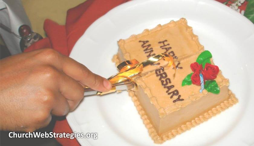 hand holding knife that's cutting an anniversary cake