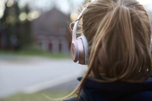 Frau trägt goldene Kopfhörer von Beats.