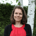 photo of Dean of Academics, Dr. Laura Spence, standing in front of a green hedge and a birch tree with white bark in spring time