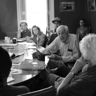 curious students sit around a table with Wendell Berry, and he explains something to a student one-on-one